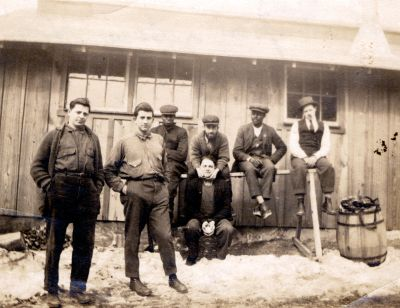 """Conscientious objectors in prison """"Lined Up on a Saw Horse"""" (l-r):<br/>'Big Fritz', Russell Keadle, Johnson, Horlacher, Strosbaugh, Watts, Stine<br/><small>William Kantor Collected Papers, Swarthmore College Peace Collection</small>"""
