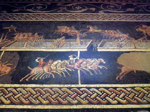 """2nd century mosaic from Lyon. The drivers wear a tunic of their faction's color. Note the water filled spina with dolphin and egg lap counters. It is even possible to see that it is the fourth lap.<br><font size=""""-2"""">Photo: Carole Raddato, Wikimedia Commons, CC BY SA</font><br><br>"""