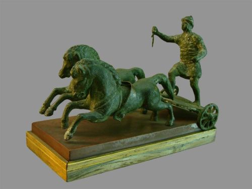 """Bronze statuette of a Roman Auriga driving a bigae (two horse chariot) from Lyon. The chariot is missing its vertical """"breast"""" portion. Notice the driver's helmet and heavy tunic.<br><font size=""""-2"""">Photo: Vassil, Wikimedia Commons, image in the public domain</font><br><br>"""