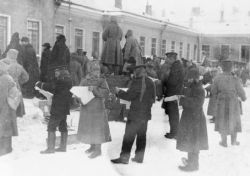 "March 1917. Military personnel and civilians read news-sheets published by the Duma after the Tsar's abdication. Soldiers and Civilians receive the first reports from the Duma after the Tsar's abdication on 2nd [15th] of March 1917. Image: Unknown photographer, <a href=""http://www.iwm.org.uk/collections/item/object/205091210"">© IWM (Q 69405).</a>"